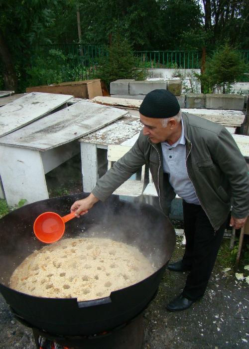 Бахтиар готовит плов для угощения верующих.