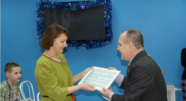 Геннадий Гарипов передал сертификат директору детского дома Наталье Поддубной.