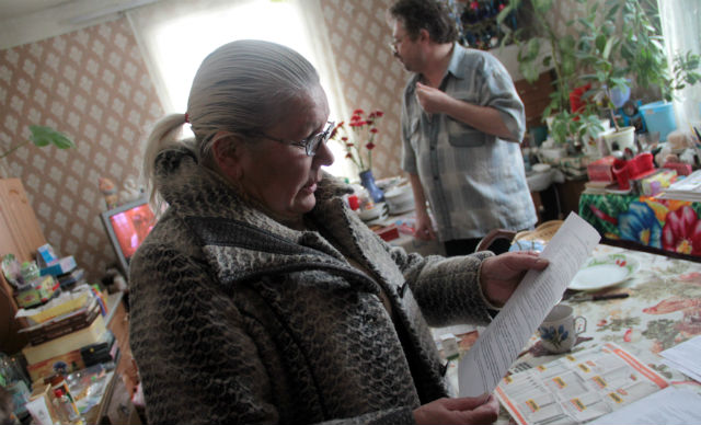 Лидия Бизяева собирает все документы, касающиеся ее дома. Еще в конце того года у нее и ее супруга была надежда, что они переедут в новый дом. Сейчас эта надежда медленно разрушается.