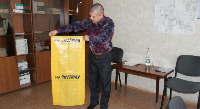 Сергей Мотин демонстрирует желтый пакет, в который отныне билимбаевцы будут собирать свой мусор.