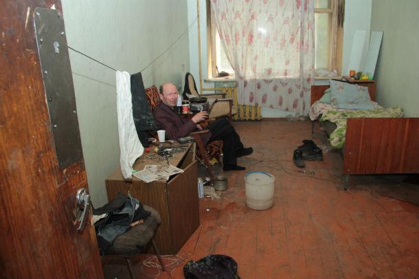 Олег Устюжанин живет в общежитии с середины 90-х. Пьет долго и упорно. Его не смущает запах в комнате, служащей ему приютом. На каком основании живет этот человек в общежитии — неясно, но, в отличие от многодетных семей, уведомления о выселении он не получал