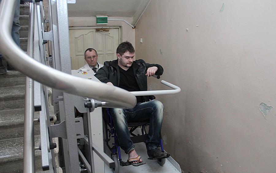Затем запускается механизм и конструкция, установленная на перилах, везет человека по лестницам Фото Анны Неволиной