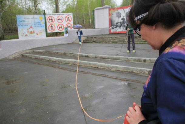 В самом начале пикета Ольга Варганова и ее группа поддержки замерили расстояние — по правилам одиночного пикета, к участнику не должны подходить люди ближе, чем на сорок метров. Фото Анны Неволиной