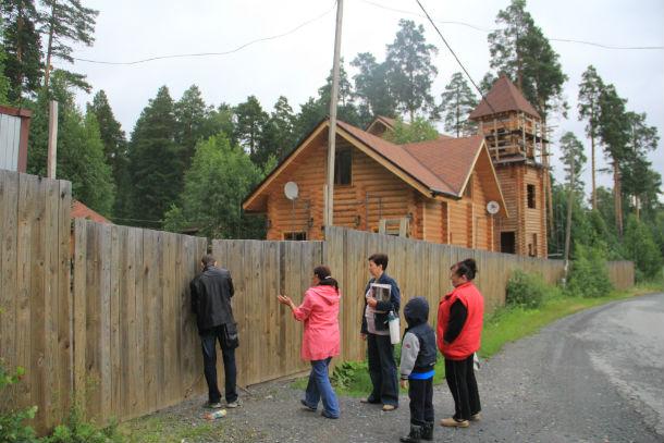 За глухим деревянным забором — домики, которые строятся в рекреационной зоне Фото Анны Неволиной