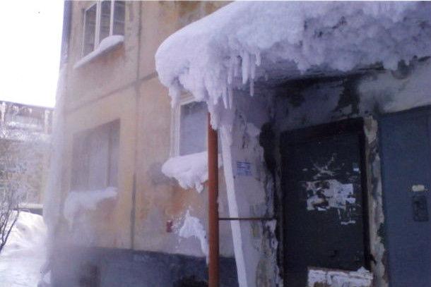 Жители дома №57/1 по улице Ватутина опасаются не только огромного снежного козырька, который образуется из-за пара, но и того, что из-за неисправных коммуникаций постоянно мокнут стены в подвале. Могут и обрушиться, считают они. Фото предоставлено Валентиной Тагильцевой