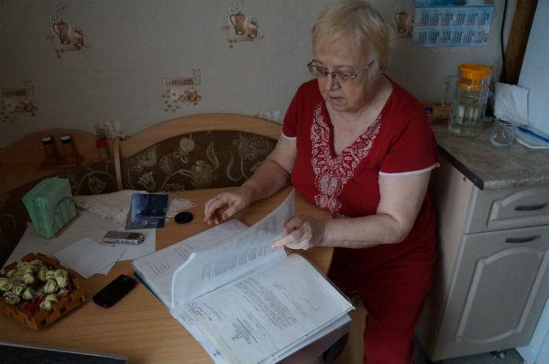 Валентина Тагильцева показывает свою многолетнюю переписку с коммунальщиками, результата от которой нет до сих пор — чиновники шлют отписки, подвал продолжает парить. Фото Олбги Хмелевой