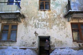 Пострадавший дом №10 улице Сакко и Ванцетти в Билимбае спустя два года после аварии не похож на жилой. Дверь в подъезд отсутствует, внутри — сквозняк. Из благ цивилизации в доме — только электроэнергия и канализация. За водой — на колонку, отопление — печное.  Фото Анны Неволиной