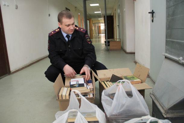 Начальник ИВС Дмитрий Кармакских рассматривает привезенные книги  Фото Анны Неволиной